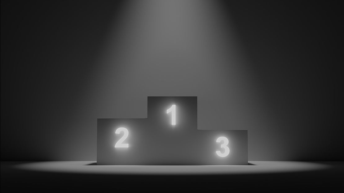 Black and white image of podium, middle is higher with a 1, left is a bit lower with a 2 and right is lowest with a 3