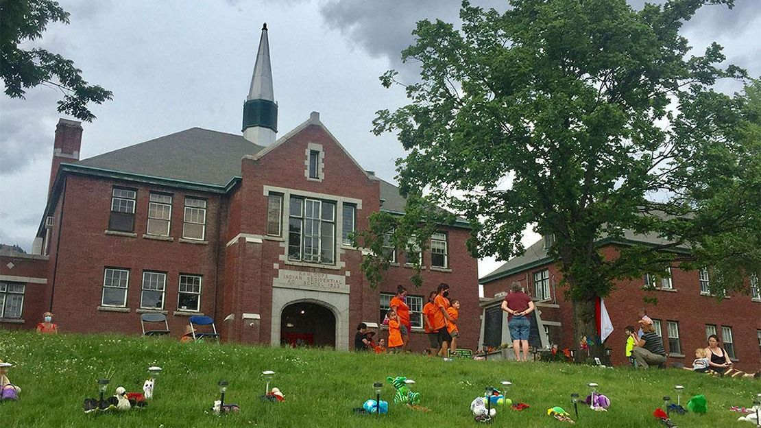 Flowers and stuffed toys on the lawn in front of the Kamloops residential school. People stand in front of the school wearing orange t-shirts.