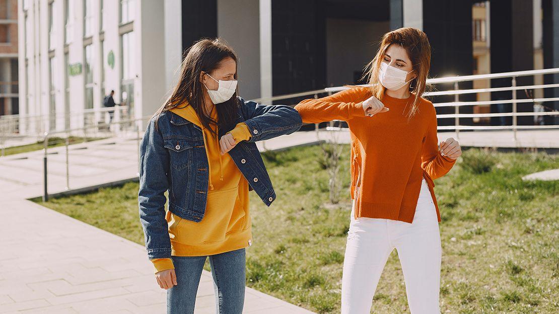 Two women wearing face masks walking next to building bumping elbows in greeting