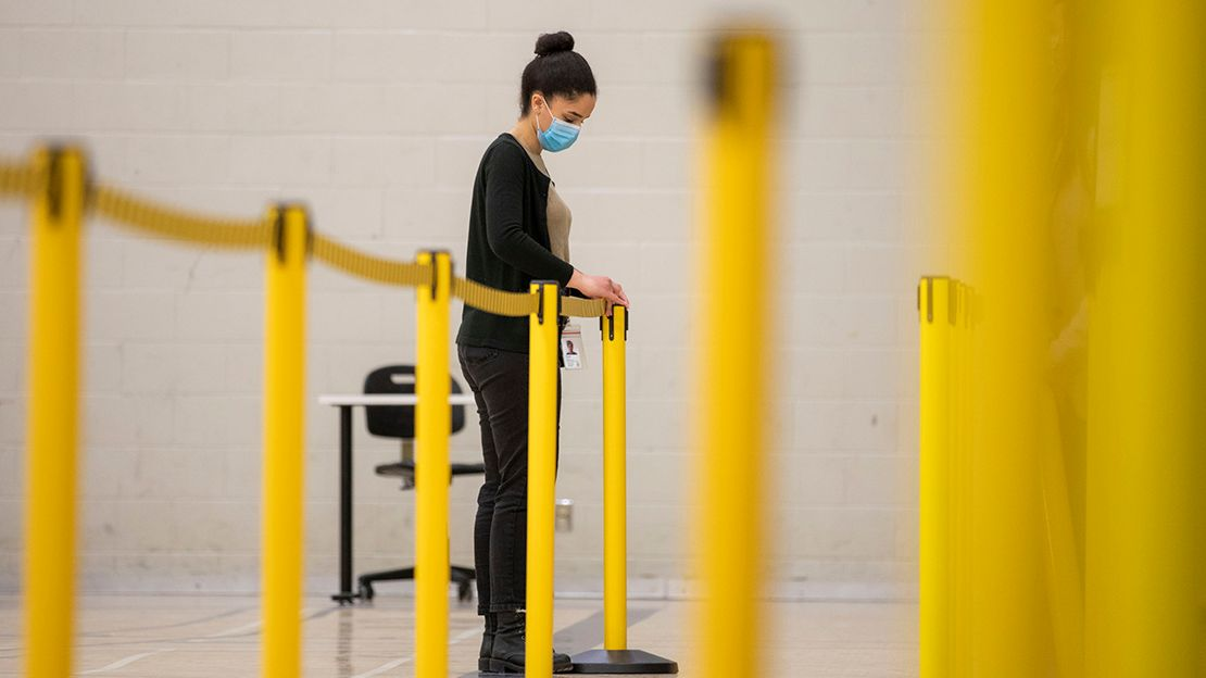 Reem El-Ajou, wearing black pants and sweater and blue surgical face mask seen in back of frame putting up yellow dividers for a queue the RAWC gym..