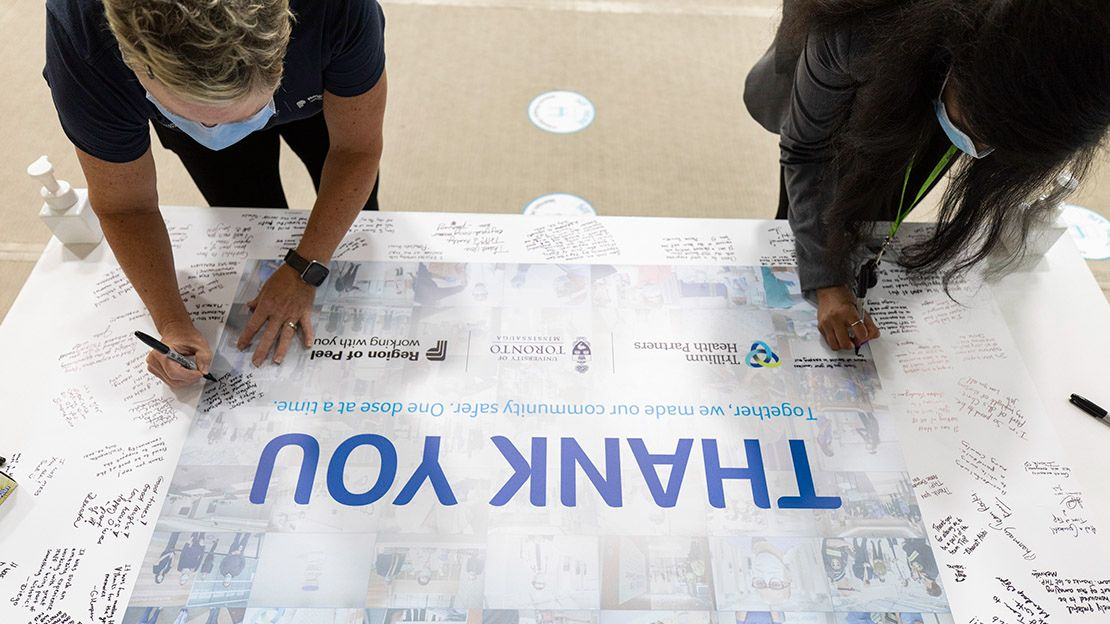 Overhead image of two women leaning over a table, writing on a large placard that contains other small, handwritten notes around the edges. In the centre is written in blue letters Thank You. Together, we made our community safer. One dose at a time.