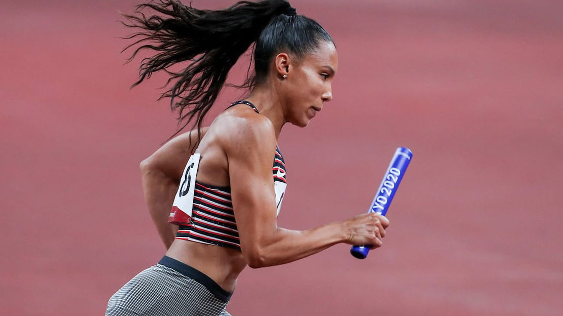 Woman running, wearing unreadable paper numbers on front and back, holding a blue baton that reads Tokyo 2020