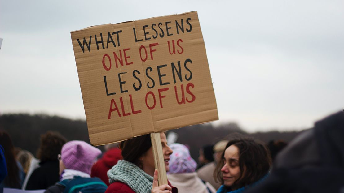 Woman holding a cardboard sign on a wooden stick that reads What lessens one of us lessens all of us