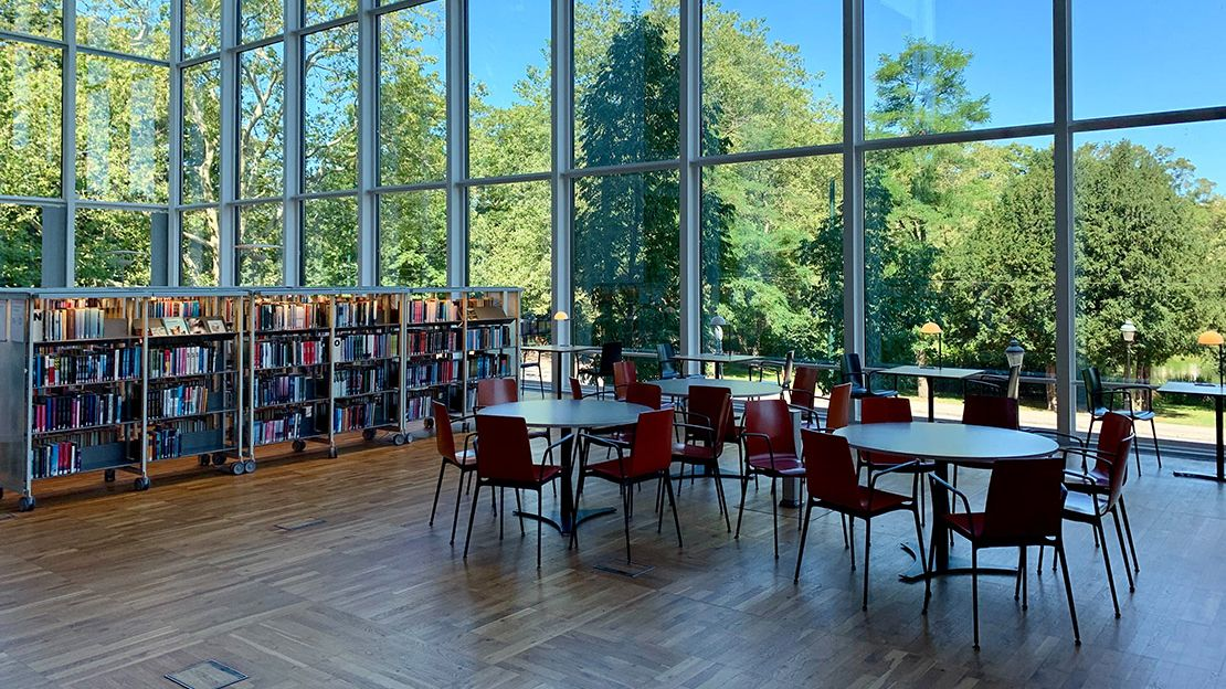 Three round tables with red chairs around them in a library, with a row of bookshelves to the left. Background shows floor-to-ceiling windows looking out to leafy green trees and a blue sky.