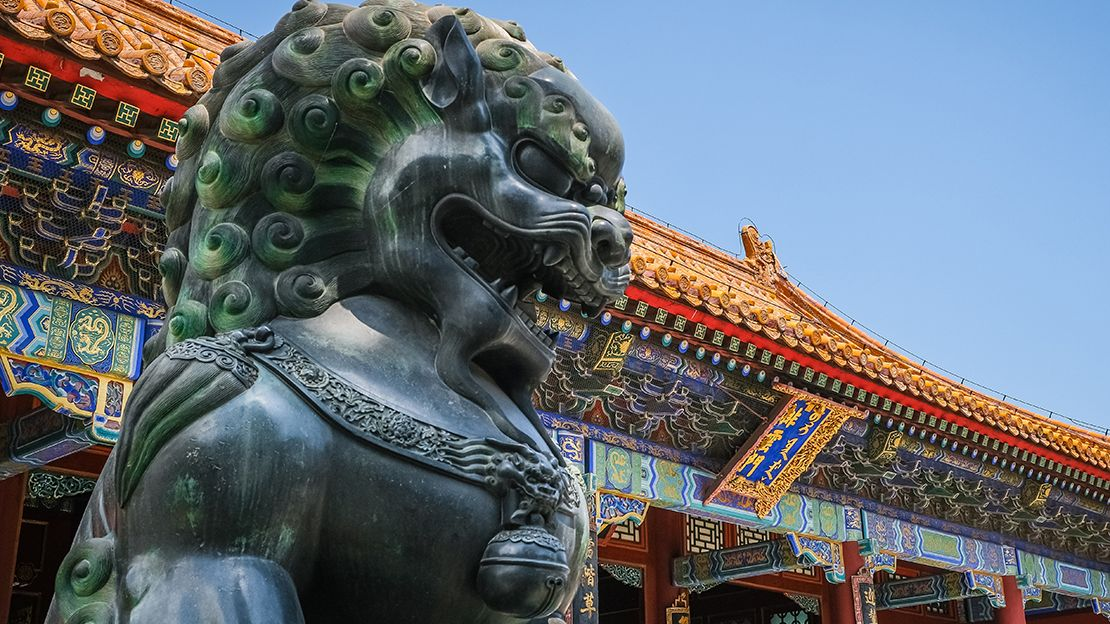 Lion sculpture with colourful Chinese temple in the background