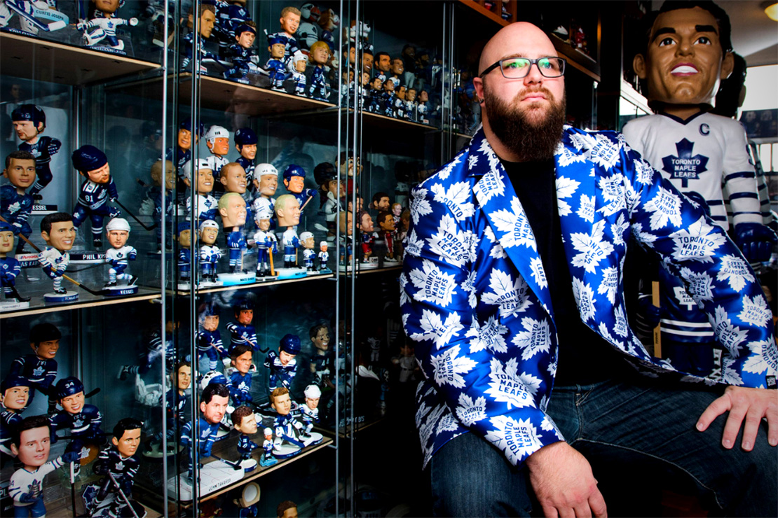 Man wearing blue suit jacket with Maple Leafs logos all over it, behind him is a glass wall cabinet along the full length of the wall holding Maple Leafs bobble heads.