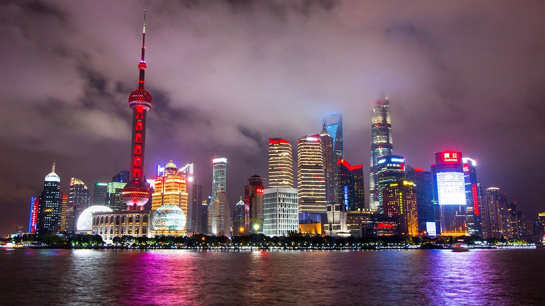 skyline of Shanghai at night, with tall tower to left illuminated by red light, multiple office towers and one tower with red lights on at the top in the shape of eyes and a mouth.