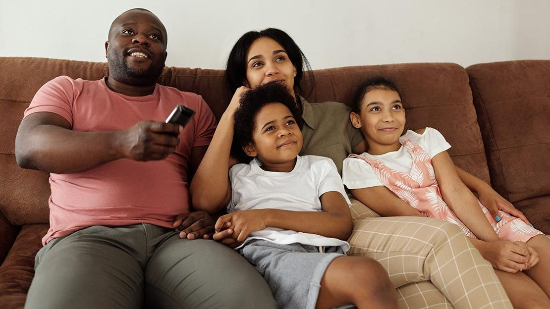 Family of four: father, mother, son and daughter, sitting on a brown couch, father holding remote pointing toward TV off screen