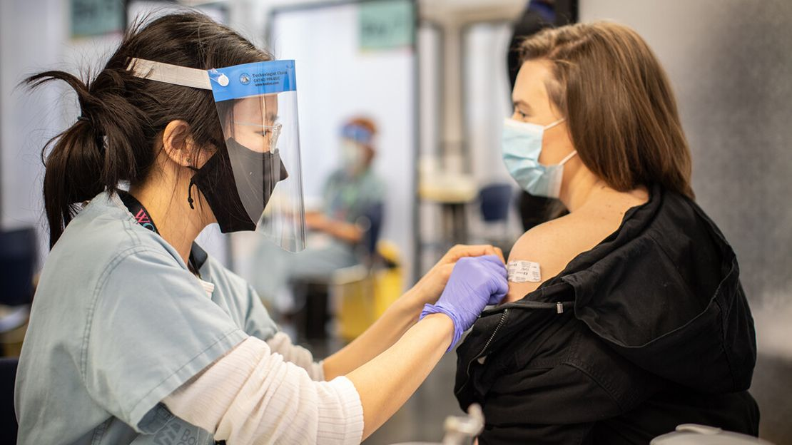 Woman wearing black face mask, face shield, blue scrubs and purple latex gloves puts a band-aid on the upper arm of another woman, who is wearing a blue face maks and black shirt, at a vaccine clinic