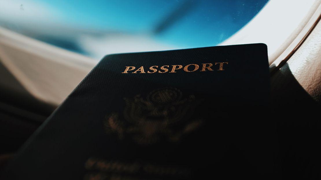 Black passport book in front of airplane window, blue sky seen through window
