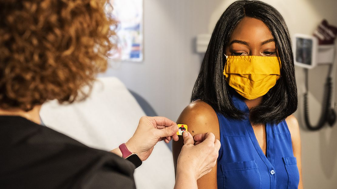 Woman in blue sleeveless shirt wearing yellow face mask gets a bandaid put on her upper arm by another woman whose back is to the camera. Background shows a doctor's office.