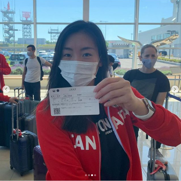 """Woman at airport wearing white face mask and red hoodie that reads """"Canada"""" on the front, holding up an airline ticket"""