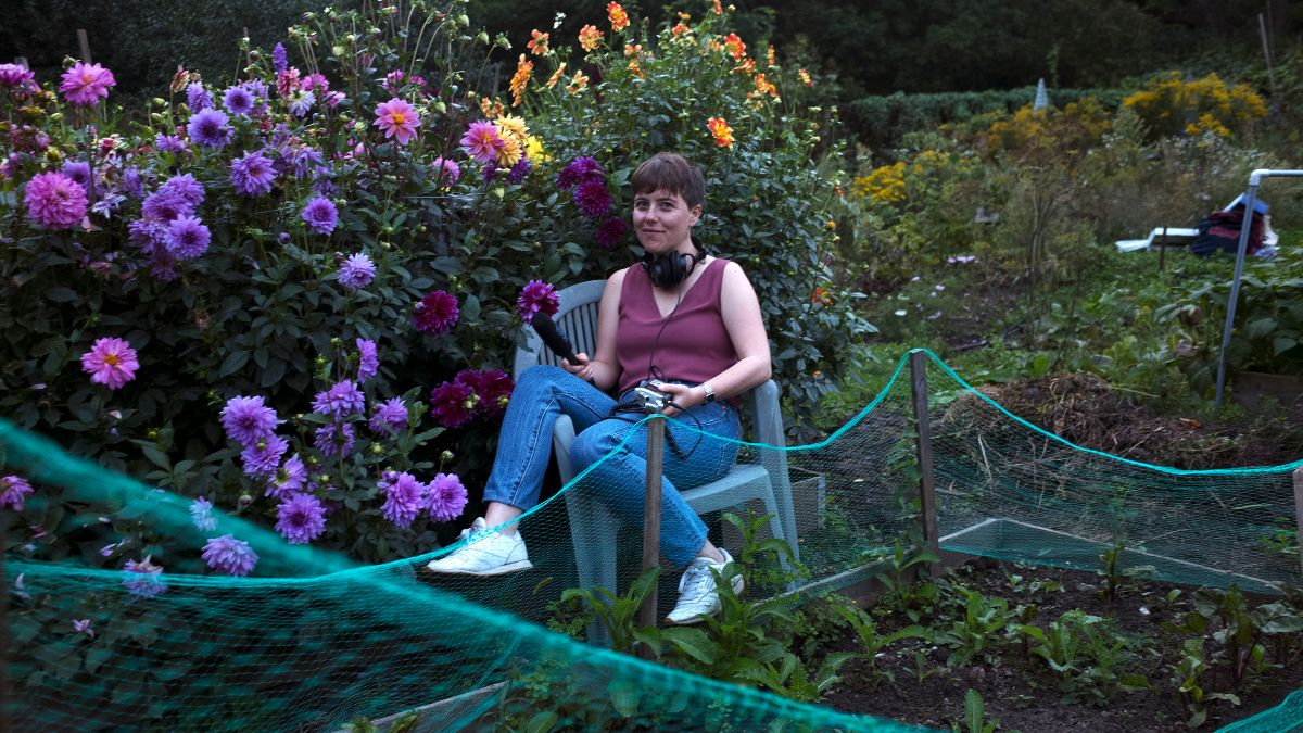 Lauren sitting on patio chair in garden, with bushes and flowers in background. She is wearing a purple sleeveless shirt, jeans and white sneakers. She has a microphone in her hand and large earphones around her neck.