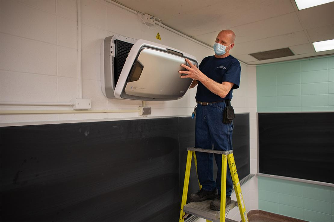 Man in jeans and blue t-shirt, wearing a paper surgical face mask, stands on a step ladder, installing an air filter unit above a blackboard.
