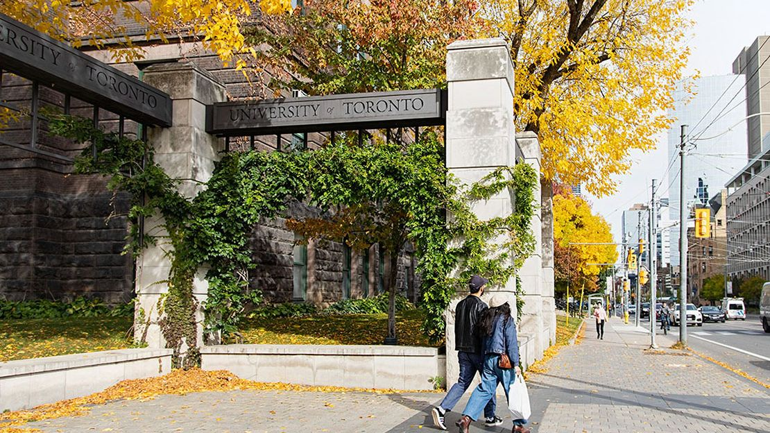 Two people walking by overhead sign between two square concrete pillars that reads University of Toronto