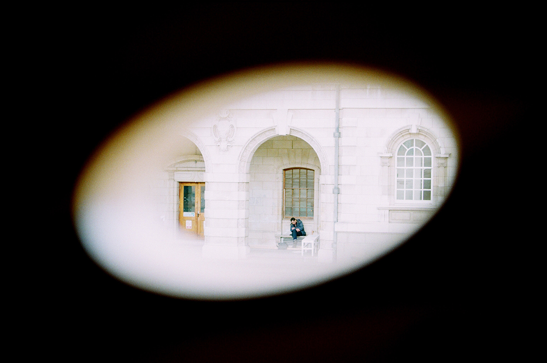 Man sitting on bench outside old stone building similar to a campus building, seen through a small circle like a spy camera