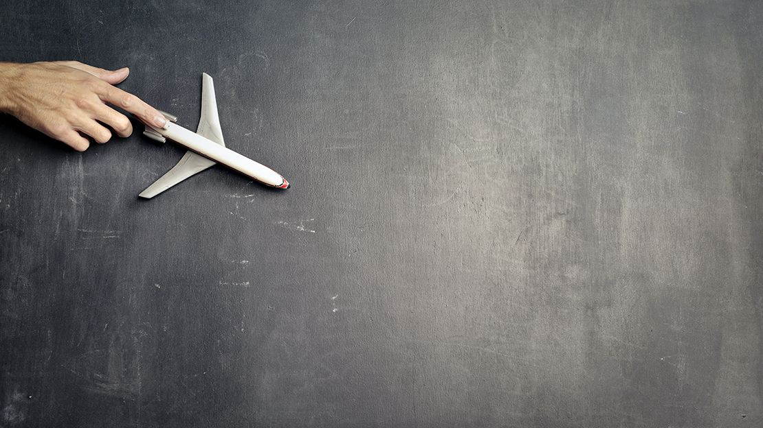 A hand holding a toy airplane against a blank chalkboard