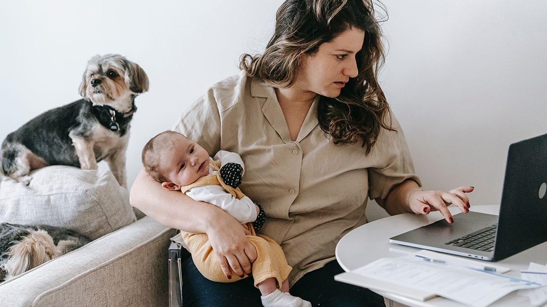 Woman sitting at table, holding a baby in one arm while working on a laptop with her other hand. In the background is a couch with a small dog on it.