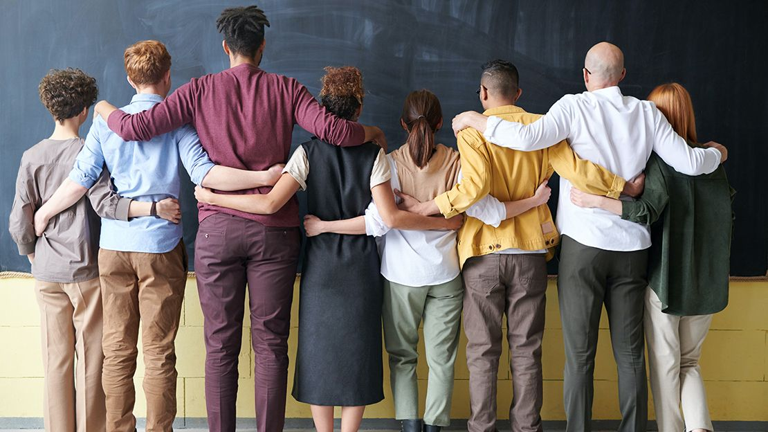 eight people of various ethnicities and mix of male and female standing with backs to camera, facing blackboard, with arms around one another