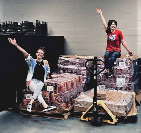 Two women wave while seated on pallets of shrink wrapped bags of Purina ONE dog food.
