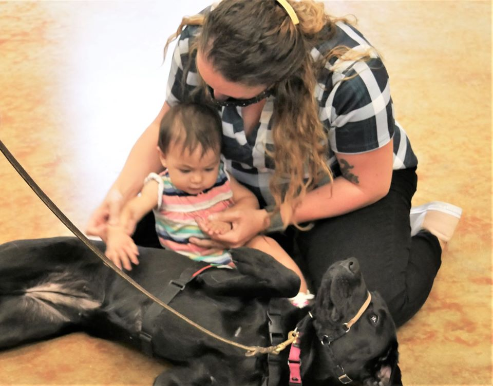 woman with 10 month old daughter on floor petting black lab who has her tummy turned up
