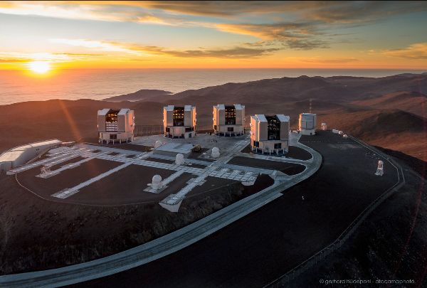 4 large cylindrical structures on a mountain top at sunset