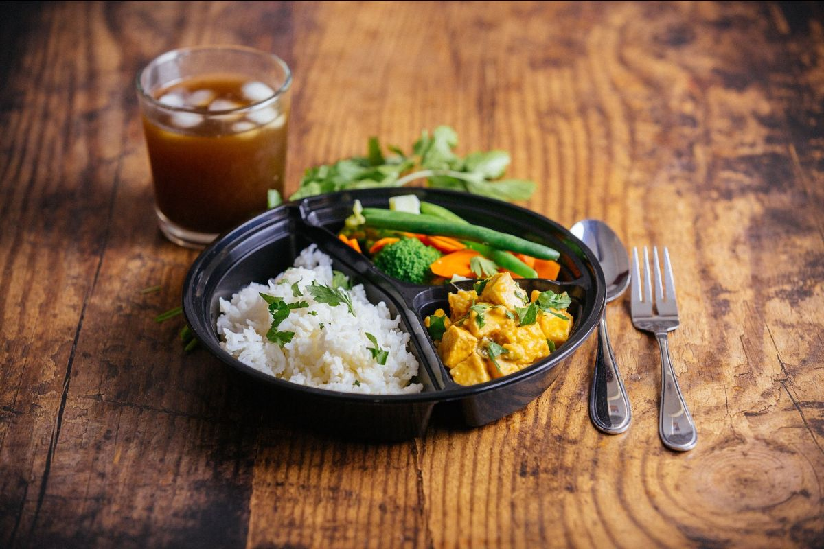 Plate of Indian food with rice, a curry, and vegetables along with silverware and a drink on a wooden surface.