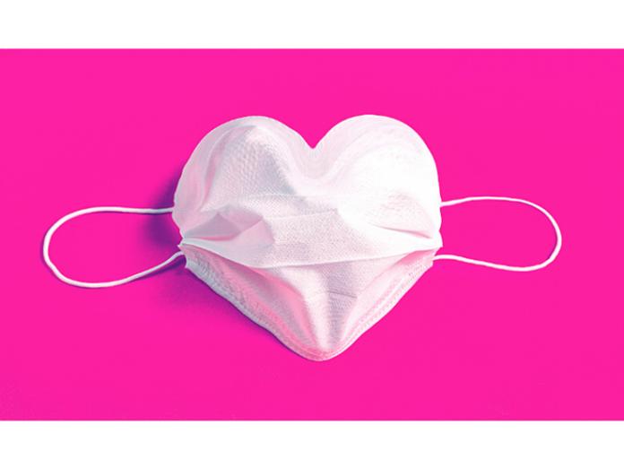 Sydämen muotoon aseteltu valkoinen maski pinkillä taustalla.