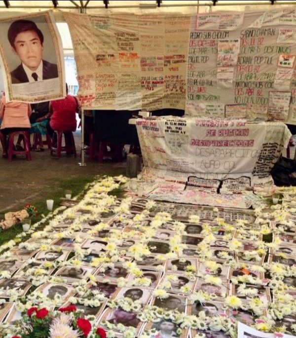 An art installation exhibits photos of the disappeared surrounded by flowers on the ground with banners reading names hanging above.