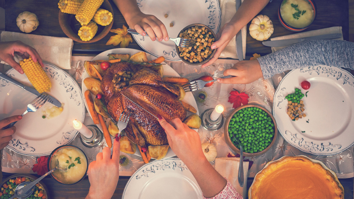 Overhead view of a kitchen table with various sets of hands reaching for traditional holiday cuisine like turkey, peas, corn on the cob and pumpkin pie.