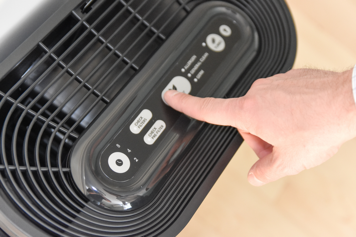 Person adjusting air purifier