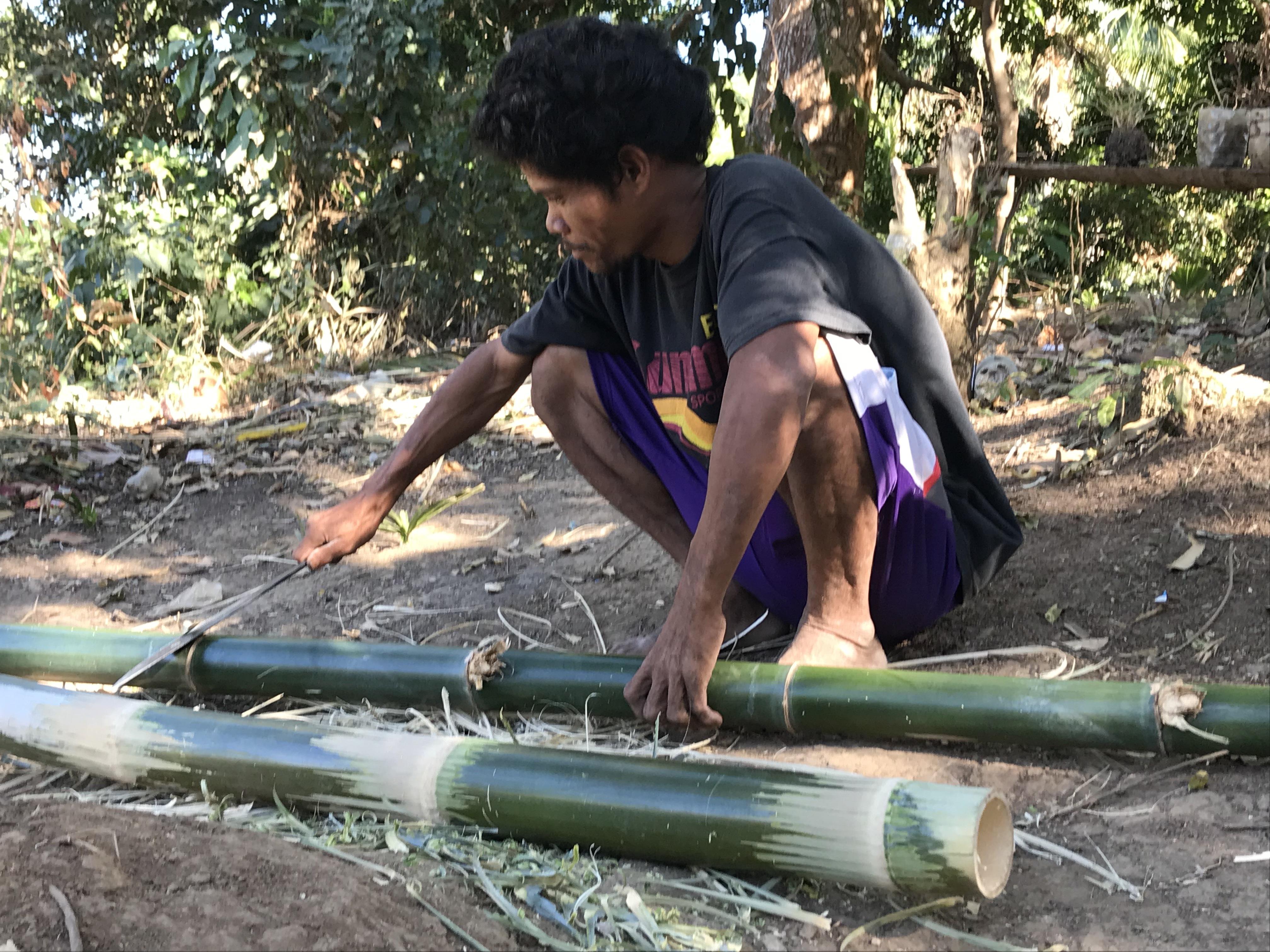 Mann bearbeitet Bambusstange
