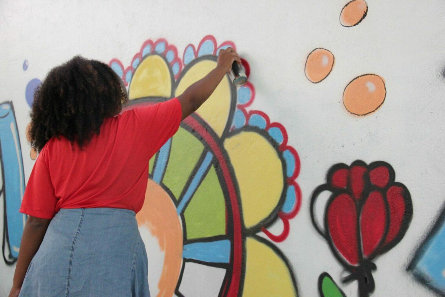 Foto de uma estudante de costas pintando uma mandala colorida em uma parede