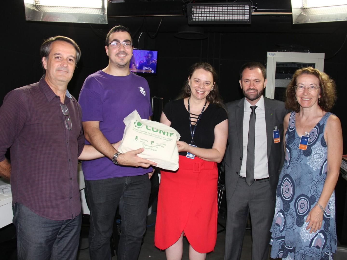 Foto de jornalistas da Gaúcha ZH, reitor e professora do IFRS com o troféu do Prêmio Conif de Jornalismo