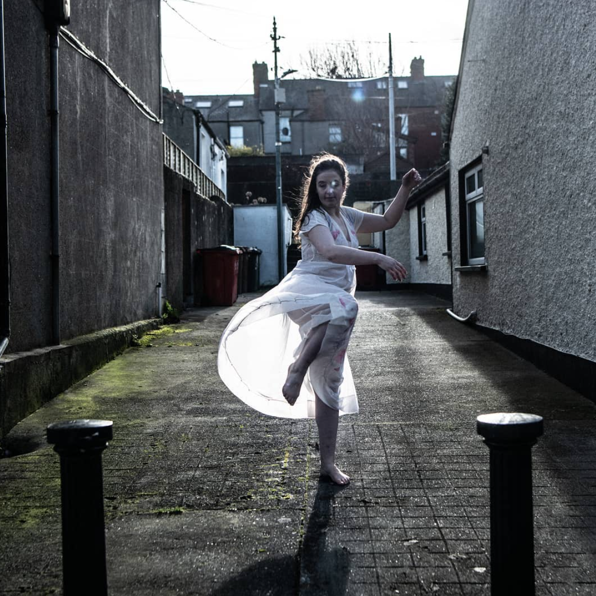 Photo of a white woman dancing in a white dress, backlit in an urban alleyway