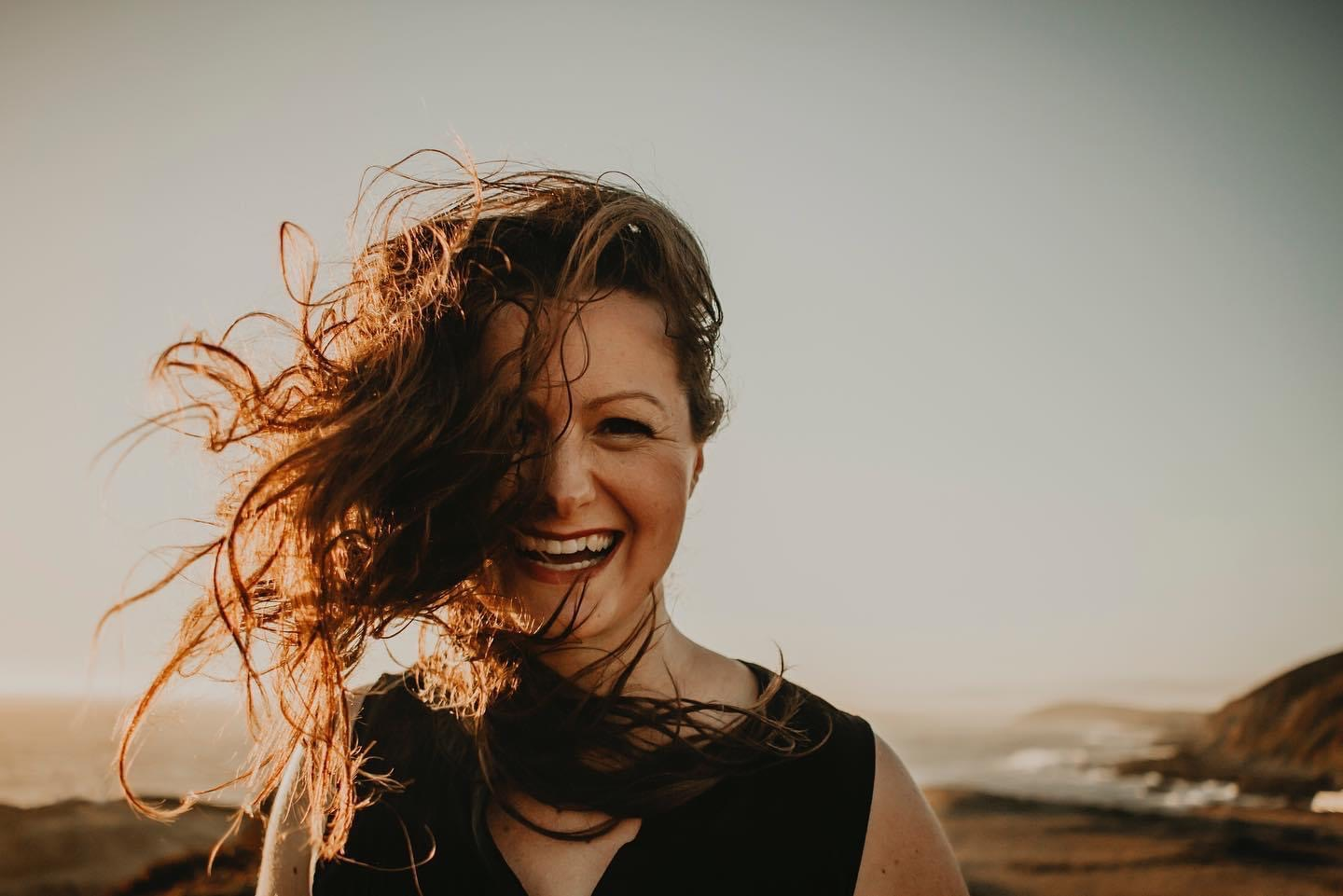 picture of a white woman looking straight into camera laughing, hair blowing messily in the wind, with the sea behind her