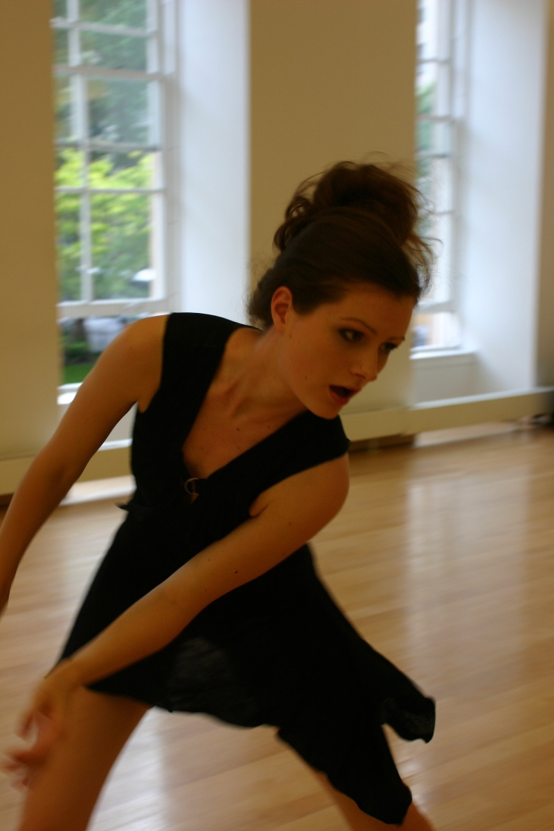 Young white woman in black dress dancing in a dance studio
