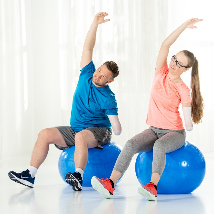 Two arm amputees exercising on blue gym balls