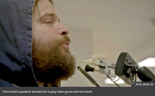 Chris Scott's quadstick allowed him to play video games with his mouth. Shows bearded Chris Scott blowing into quadstick