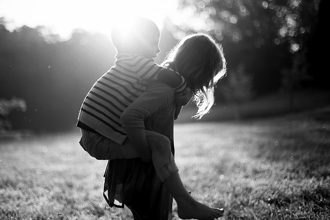 Black and white photo of girl giving boy a piggy-back