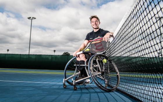 A smiling Alfie Hewett in his sports wheelchair holding a tennis racquet