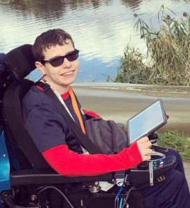 Beth Moulam sitting in her powered wheelchair by a lake, smiling at the camera and looking very cool with her shades on!