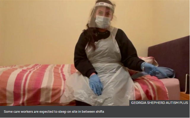 Care worker in full PPE sitting on the side of a bed