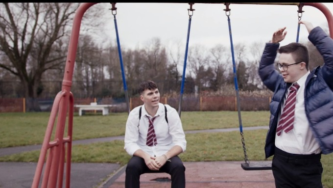 Photo of two of the film's characters by swings in a playground