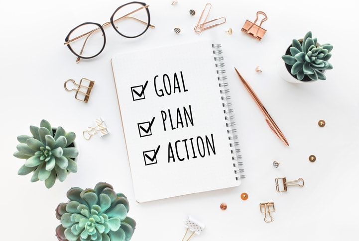 notebook with 'goal, plan, action' written in it with odds and ends all around it