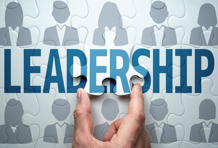 hand putting together puzzle pieces with business people on them and the word 'LEADERSHIP'