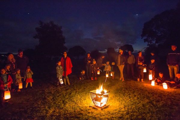 Children from the Kuaotunu Kindergarten gathered around a fire at night celebrating their Lantern Festival