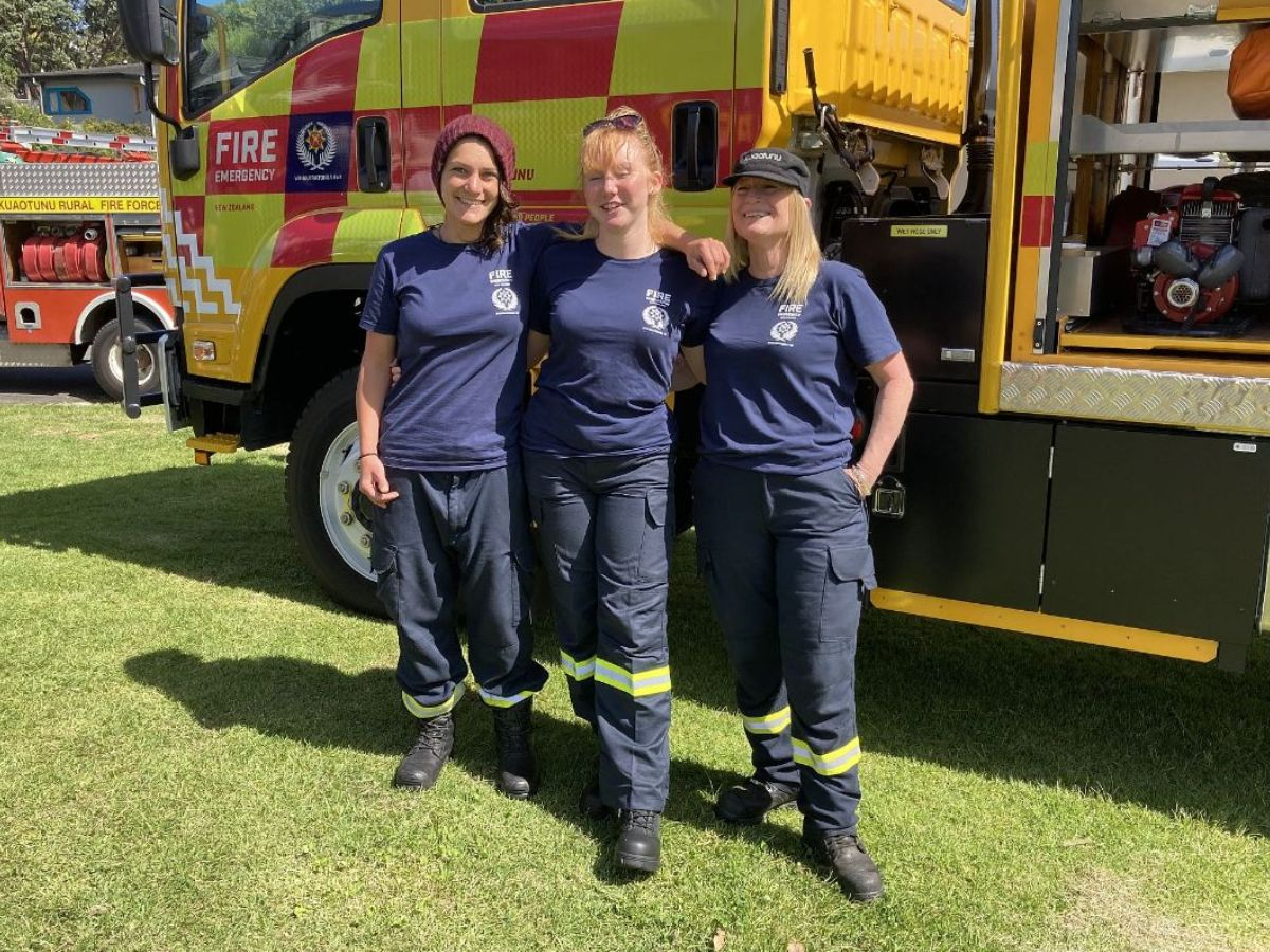Lauren Agopian, Lily Nielsen and Fiona Simpson standing beside Kuaotunu FENZ's new fire appliance