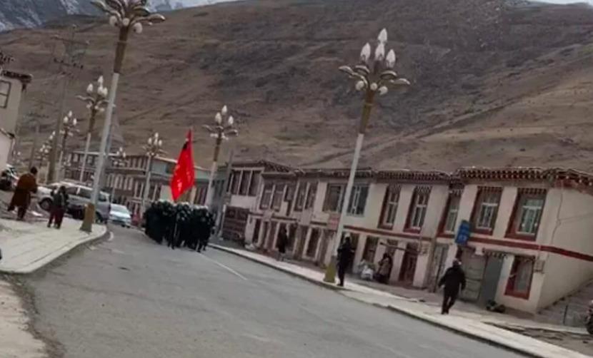 Foto van een straat in Oost-Tibet waar een grote groep Chinese soldaten met een CCP-vlag marcheren door de straten