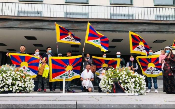 Foto van Tibetanen in Nederland die Tibetaanse vlaggen omhoog houden voor de actie #FlagsforTibet